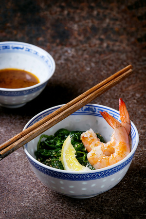 chinese spinach: Chinese bowls with Cooked spinach and fried shrimps prawns with lemon and sesame seeds, soy sauce and chopsticks over old iron background. Asian style dinner.