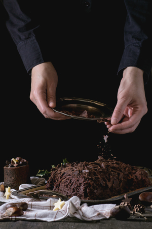 yule: Decorating process of homemade Christmas chocolate yule log by womans hands with chocolate chips over old wooden table with holly branch and chestnuts. Dark rustic style.