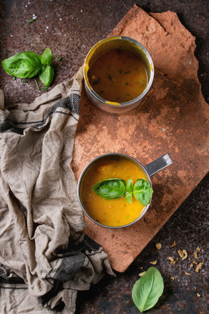 prepack: Iron mug of carrot soup from can, served with fresh basil, fried onion, empty tin can and kitchen towel on clay board over old rusty iron background. Dark rustic style. Top view