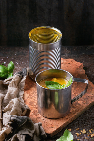prepack: Iron mug of carrot soup from can, served with fresh basil, fried onion, empty tin can and kitchen towel on clay board over old rusty iron background. Dark rustic style