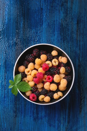 Bowl of colorful yellow and red raspberries and black dewberry with leaf over blue wooden textured background. Top view with copy space. Stock Photo
