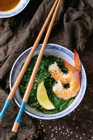 chinese spinach: Chinese bowls with Cooked spinach and fried shrimps prawns with lemon and sesame seeds, soy sauce and chopsticks on sackcloth over old iron background. Asian style dinner. Top view Stock Photo