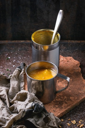 prepack: Iron mug of carrot soup from can, served with empty tin can and kitchen towel on clay board over old rusty iron background. Dark rustic style