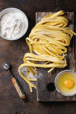 wood cutter: Raw uncooked homemade italian pasta tagliatelle with, pasta cutter, bowls with white flour and broken egg on old wood cutting board over dark wooden background. Top view with space for text