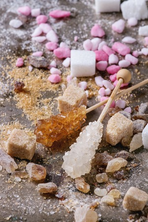 Variety of sugar white, brown pink fruit granulated, cubes and crystal over old texture iron background. Close up Stock Photo