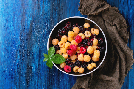 spot the difference: Bowl of colorful yellow and red raspberries and black dewberry with leaf on sackcloth rag over blue wooden textured background. Top view with copy space.