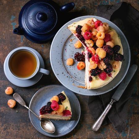 gâteau nu Semi et morceau de gâteau à la crème de citron, décoré par des framboises jaunes colorés rouges et ronce frais, servi avec du thé sur le gâteau gris debout sur fond sombre du bois. vue de dessus Banque d'images