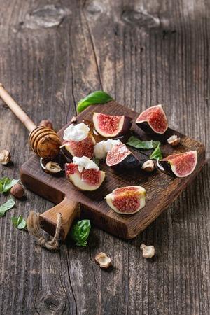 Figues fraîches tranchées avec fromage ricotta, feuilles de basilic, noisette et miel de la louche sur la petite planche à découper en bois sur fond de bois foncé. Banque d'images