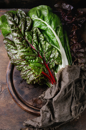 Variety of fresh chard mangold salad leaves on wood chopping board with sackcloth rag over old dark wooden background. Top view with space for text.