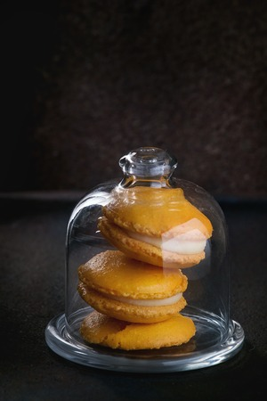 Orange lemon homemade macaroons with white chocolate in glass bell jar over black textural.