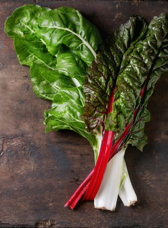 Variety of fresh chard mangold salad leaves over old dark wooden background. Top view with space for text. Healthy eating theme.