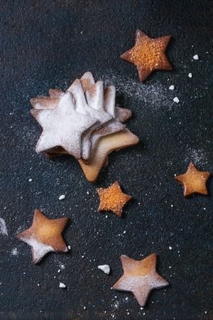 textural: Homemade shortbread star shape sugar cookies different size with sugar powder on black textural surface. Christmas treats background. Overhead view