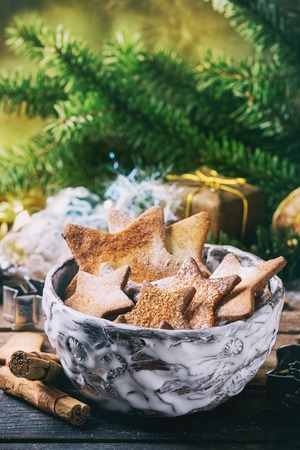 sugar cookie: Bowl of homemade Christmas shortbread star shape sugar cookies different size with sugar powder and cookie cutters on old wooden surface with Christmas decor and fir tree at background. Retro filter