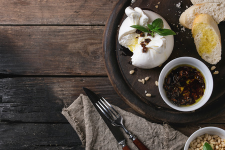 Sliced Italian cheese burrata served on round chopping board with pine nuts, sliced bread, basil and dried tomatoes in olive oil with fork and knife over old wood background. Overhead view