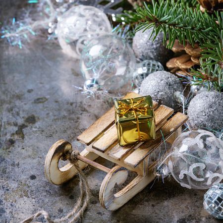 metall texture: Christmas decoration card with glass and wooden toys, gift, cones and green tree over old dark metal background. Gifts on sled. Copy space for text. Square image Stock Photo