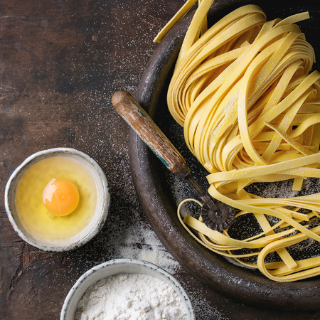 Raw uncooked homemade italian pasta tagliatelle with pasta cutter, bowls with white flour and broken egg in old clay tray over dark wooden background. Top view with space for text. Square image Stock Photo