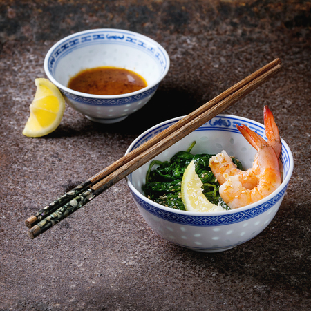 chinese spinach: Chinese bowls with Cooked spinach and fried shrimps prawns with lemon and sesame seeds, soy sauce and chopsticks over old iron background. Asian style dinner. Square image