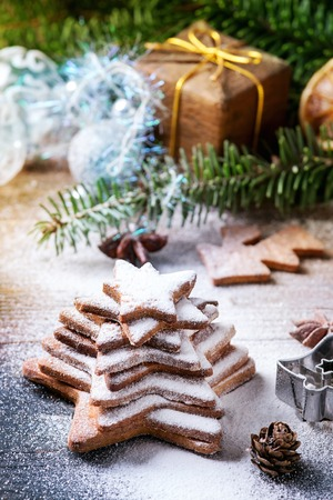 Stack of homemade Christmas shortbread star shape sugar cookies different size with sugar powder on old wooden surface with Christmas decor and fir tree at background.