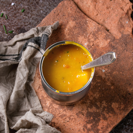 prepack: Tin can of carrot soup with spoon, standing on kitchen towel  and clay board over old rusty iron background. Dark rustic style. Overhead view. Square image