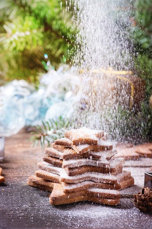 sprinkling: Stack of homemade Christmas shortbread star shape sugar cookies different size with sprinkling sugar powder on old wooden surface with Christmas decor and fir tree at background. Stock Photo
