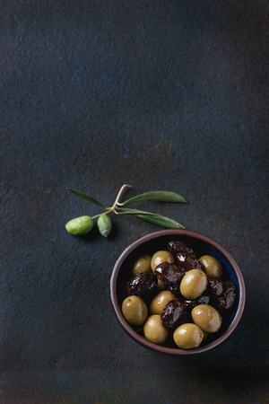 textural: Bowl of green and black olives with young olives branch over black textural background. Overhead view with space for text