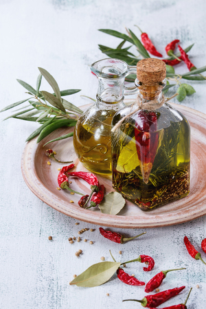 Glass bottle and jug of spicy and normal olive oil with rosemary, red hot chili peppers and bay leaf standing on ceramic plate with olives branch over white wooden background. Mediterranean style
