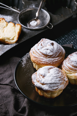 textil: Modern pastries cruffins, whole and slice, like croissant and muffin with sugar powder, served on black plate with sieve, silicon baking form and textil napkin over dark texture background.