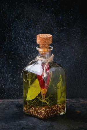 textural: Glass bottle of spicy olive oil with rosemary, red hot chili peppers and bay leaf standing over black textural background. Mediterranean style Stock Photo