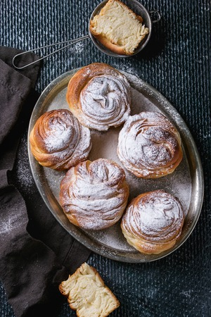 textil: Modern pastries cruffins, whole and slice, like croissant and muffin with sugar powder, served on vintage metal tray with sieve and black textil napkin over dark texture background. Top view