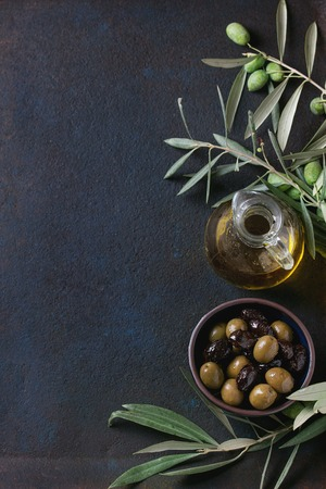 Bowl of green and black olives with young olives branch and bottle of olive oil over black textural background. Overhead view with space for text