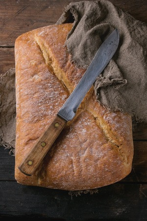 artisan bakery: Whole fresh baked artisan bread under sackcloth with vintage knife over old wooden background. Overhead view. Stock Photo