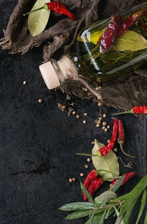 textural: Glass bottle of spicy olive oil with rosemary, red hot chili peppers and bay leaf lying on sackcloth rag with olives branch over black textural background. Mediterranean style. Top view Stock Photo