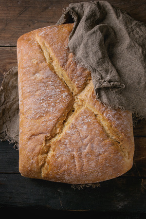 artisan bakery: Whole fresh baked artisan bread under sackcloth over old wooden background. Dark rustic style. Overhead view. Stock Photo