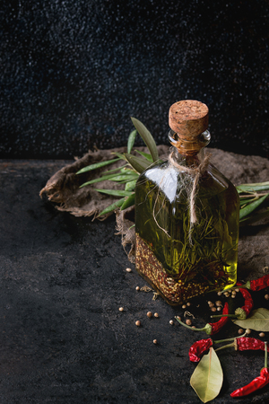 textural: Glass bottle of spicy olive oil with rosemary, red hot chili peppers and bay leaf standing on sackcloth rag with olives branch over black textural background. Mediterranean style Stock Photo