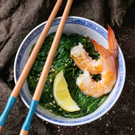 chinese spinach: Chinese bowls with Cooked spinach and fried shrimps prawns with lemon and sesame seeds, soy sauce and chopsticks on sackcloth over old iron background. Asian style dinner. Top view. Square image