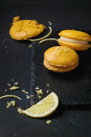Whole and broken orange lemon homemade macaroons with white chocolate, lemon slice and zest and citrus sugar on stone slate board over black textural background. Stock Photo