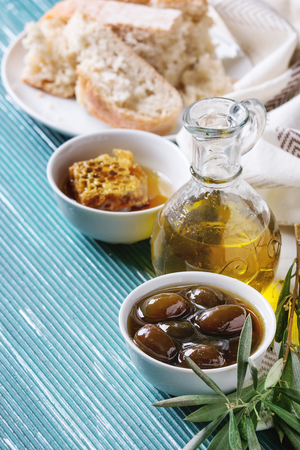 space for text: Bowls with sweet green olives in honey sauce and honeycombs, served on white textile with bottle of olive oil, sliced bread and olive branch over turquoise texture background. Space for text