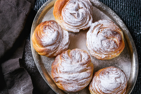 textil: Modern pastries cruffins, like croissant and muffin with sugar powder, served on vintage metal tray with black textil napkin over dark texture background. Overhead view