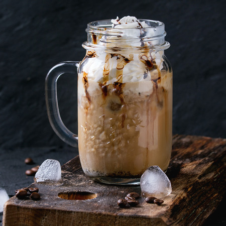 cold background: Glass mason jar with ice coffee with whipped cream, ice cream and chocolate sauce, served with coffee beans and ice cubes on wooden chopping board over black textured background. Square image