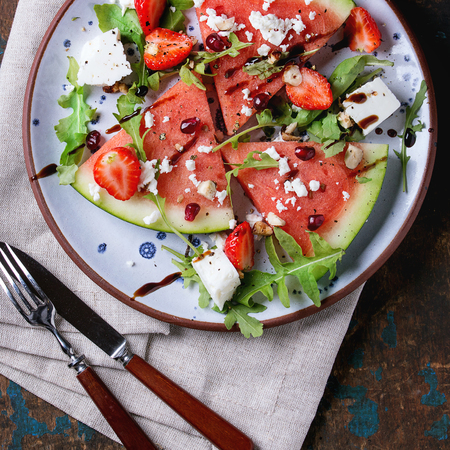 Blue spotted plate with watermelon and strawberry fruit salad with feta cheese, arugula, nuts and balsamic sauce, served with fork, knife and napkin over old dark wood background. Top view. Square image Stock Photo