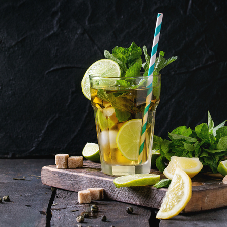 alcochol: Glass of Iced green tea with lime, lemon, mint and sugar cubes on wooden chopping board over old wooden table. Dark rustic style. Square image