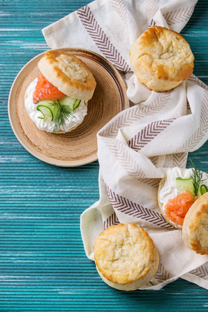 Sliced traditional english cheese scones with smoked salmon, creme cheese and fresh cucumber served with whole scones on white kitchen towel over turquoise texture background. Top view