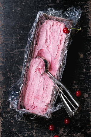 polyethylene film: Homemade cherry sorbet in vintage iron container with polyethylene film, fresh cherry berries and metal spoon for ice cream over old black wooden textured background. Top view