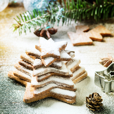 Stack of homemade Christmas shortbread star shape sugar cookies different size with sugar powder on old wooden surface with Christmas decor and fir tree at background. Toned. Square image Stock Photo