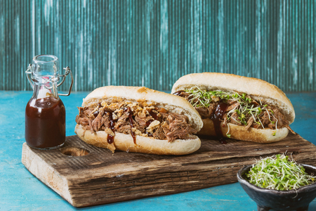 pulled over: Variety of pulled pork sandwiches with meat, fried onion, green sprouts and bbq ketchup, served on wood cutting board with small bottle of tomato sauce over bright blue wooden background. Toned image