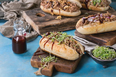 pulled over: Variety of pulled pork sandwiches with meat, fried onion, green sprouts and bbq ketchup, served on wood cutting board with small bottle of tomato sauce over bright blue wooden background. Stock Photo