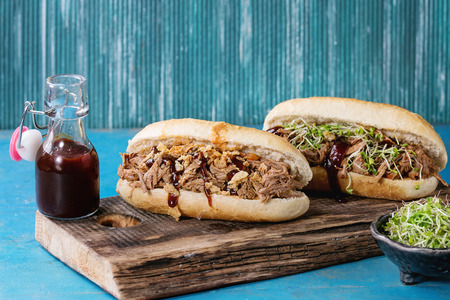 ketchup bottle: Variety of pulled pork sandwiches with meat, fried onion, green sprouts and bbq ketchup, served on wood cutting board with small bottle of tomato sauce over bright blue wooden background. Stock Photo