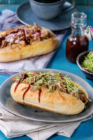 pulled over: Variety of pulled pork sandwiches with meat, fried onion, green sprouts and bbq ketchup, served on gray plate with small bottle of tomato sauce and cup of coffee over bright blue wooden background. Stock Photo