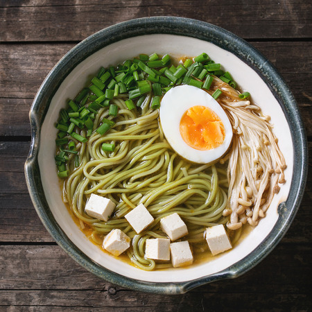 Ceramic bowl of asian style soup with green tea soba noodles, half of egg, mushrooms, spring onion and tofu cheese, served over old wooden background. Top view. Square image