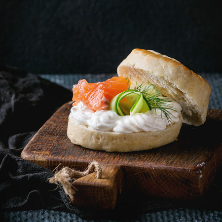 Sliced traditional english cheese scones with smoked salmon, creme cheese and fresh cucumber served on wooden chopping board over black texture background. Close up. Square image